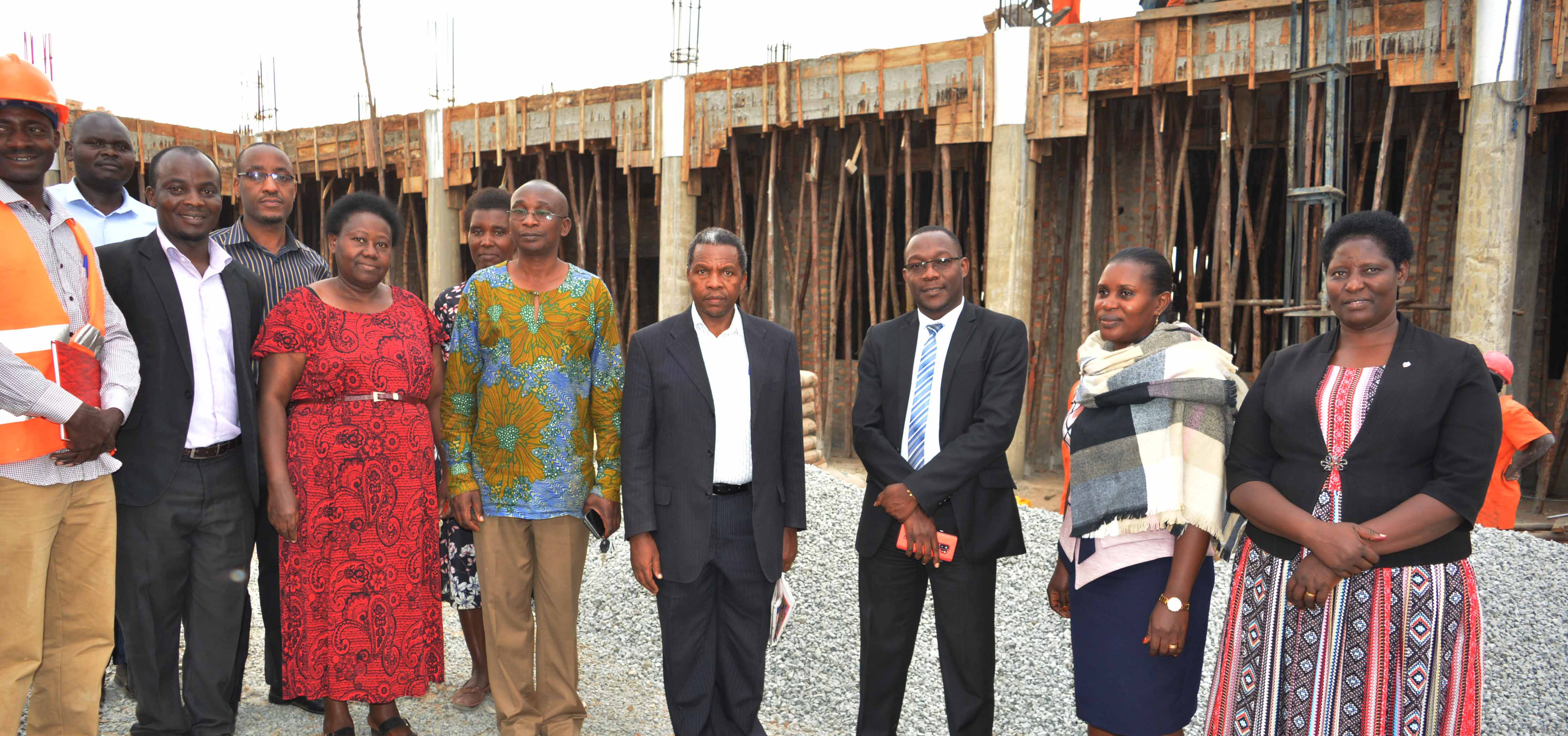 Ministry of Education and Sports officials posing for a photo with the university top management at the Science Laboratory construction site