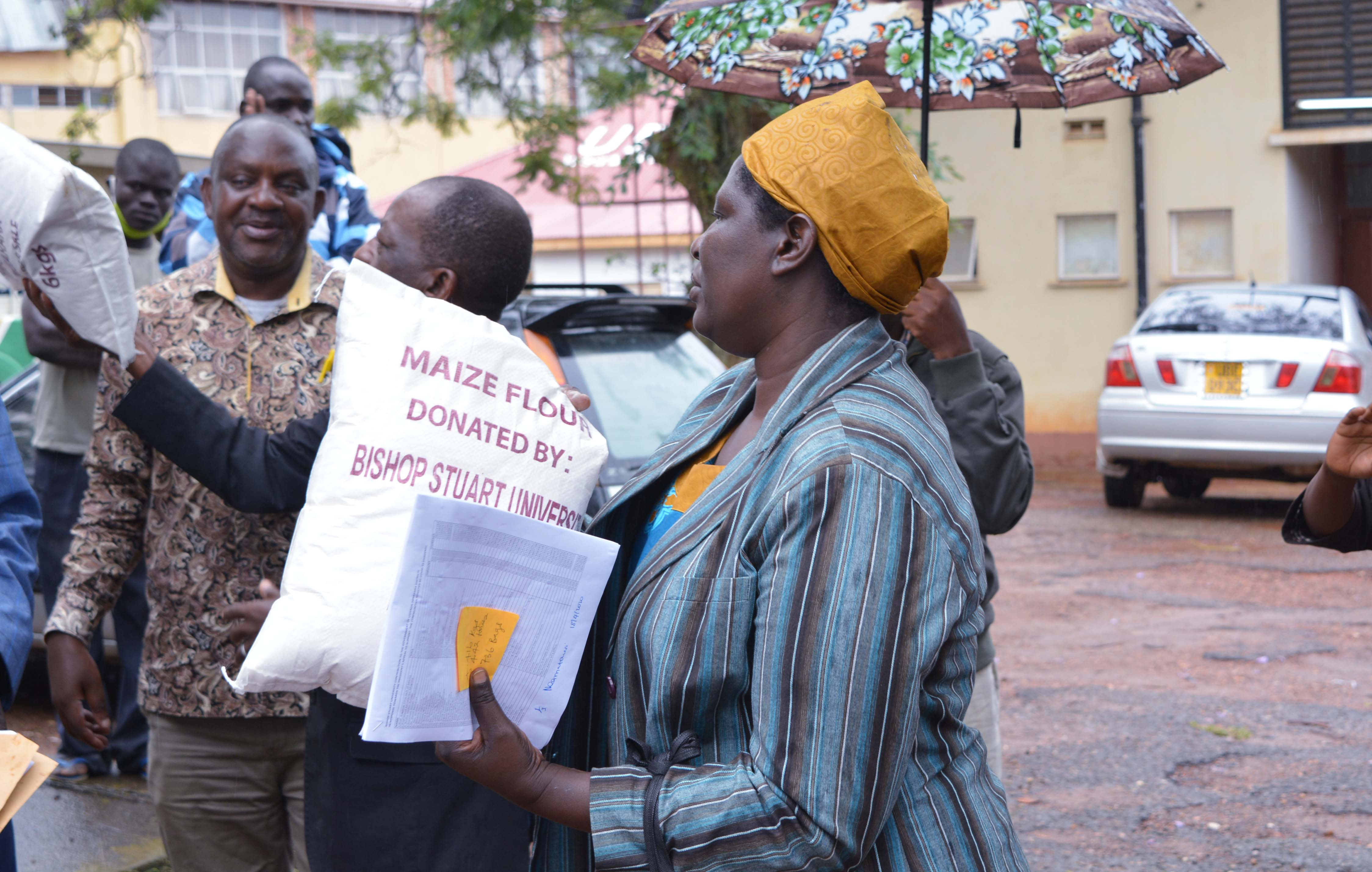 Prof. Maud Kamatenesi handing over a sack of maize flour