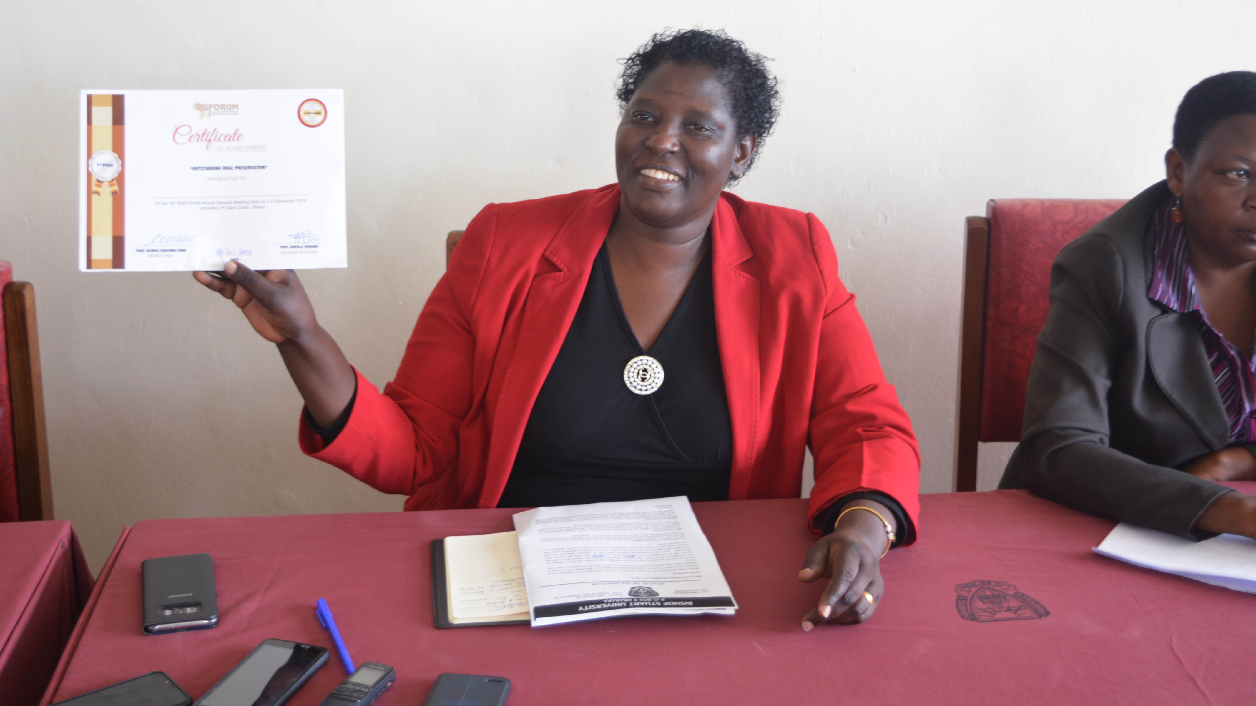 VC Prof. Maud Kamatenesi (PhD) showing a certificate of achievement presented to Bishop Stuart University by RUFORUM