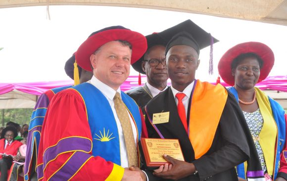 Prof. Philp Laird, Ph.D. of TWU shaking hands with a first class student from the Faculty of Education (then) on the 13th Graduation Ceremony- 13/10/2017, right is VC, Prof. Maud Kamatenesi Mugisha Ph.D.